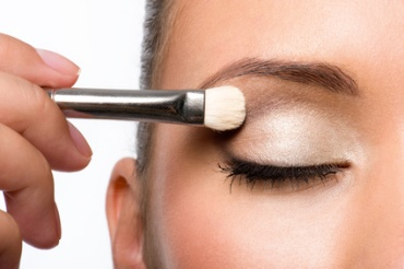 woman applying eyeshadow on eyelid using makeup brush